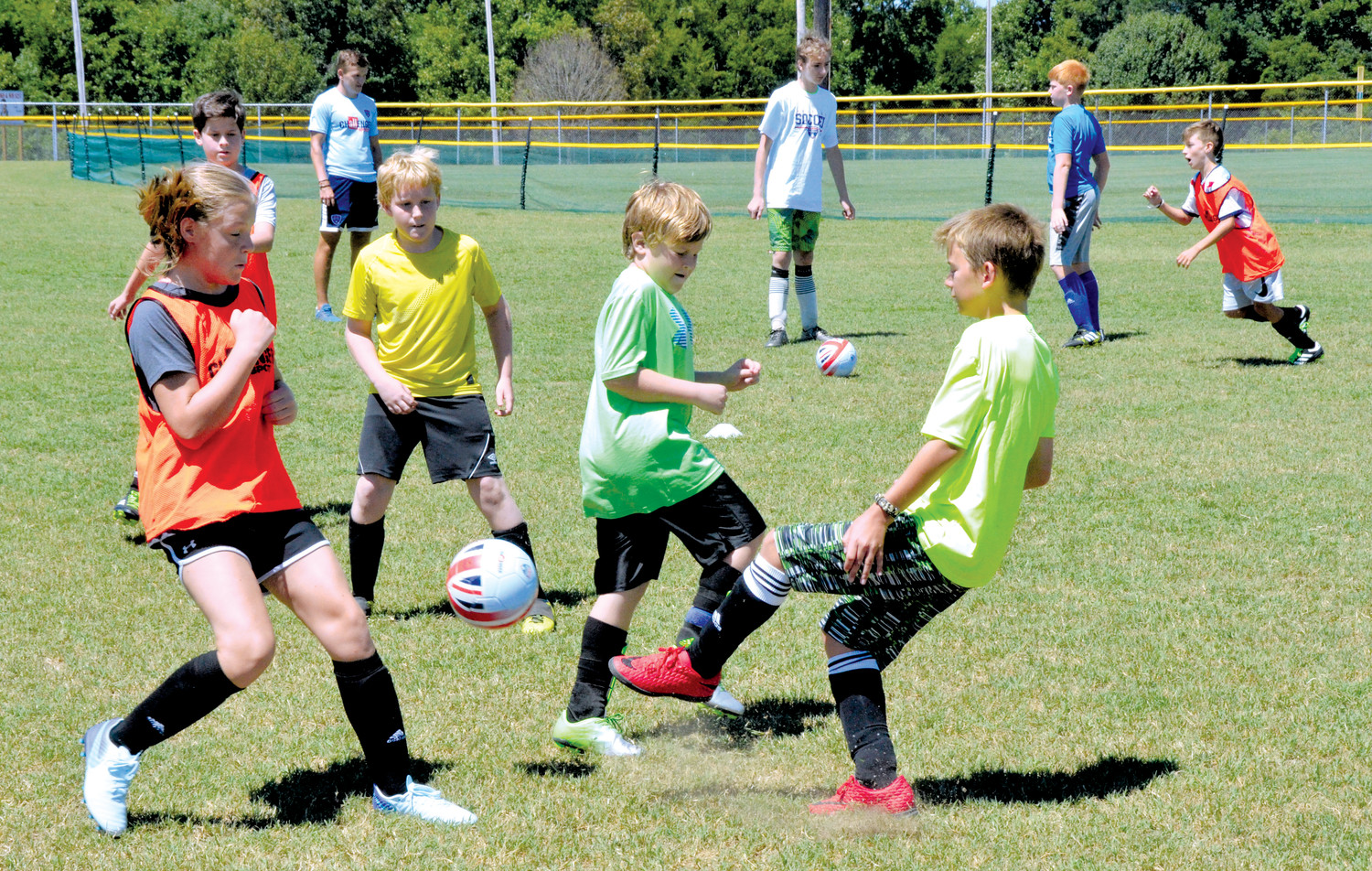 Cameron Denning, left, attempts to block a clearing pass from goalkeeper Braston Autry, right. Nicholas Jackson defends in the background, while Braeden Kesler and Connor Parker work to get open on offense. This drill was a part of a 3-on-3 'World Cup' game simulation at the Challenger Sports British Soccer Camp that began yesterday morning.