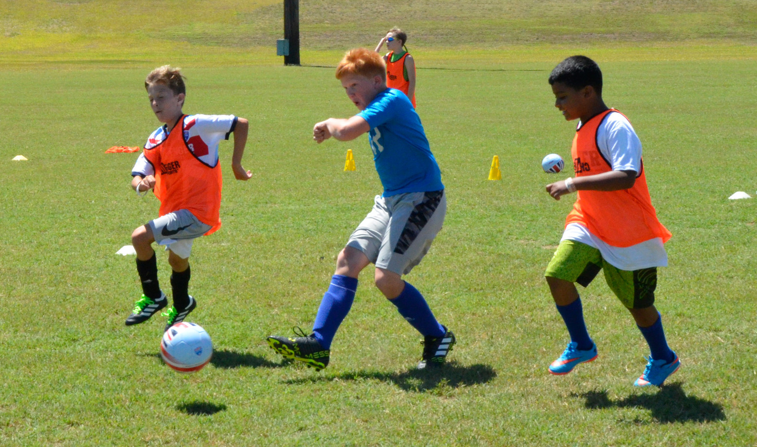 Walker Holmes blasts a shot onto goal after breaking away from Thomas Honeycutt, left, and Elijah Moore, right. This shot on goal took place Monday duringa  3-on-3 game-simulation training arranged by Challenger Sports British Soccer Camp instructor James McIvor.