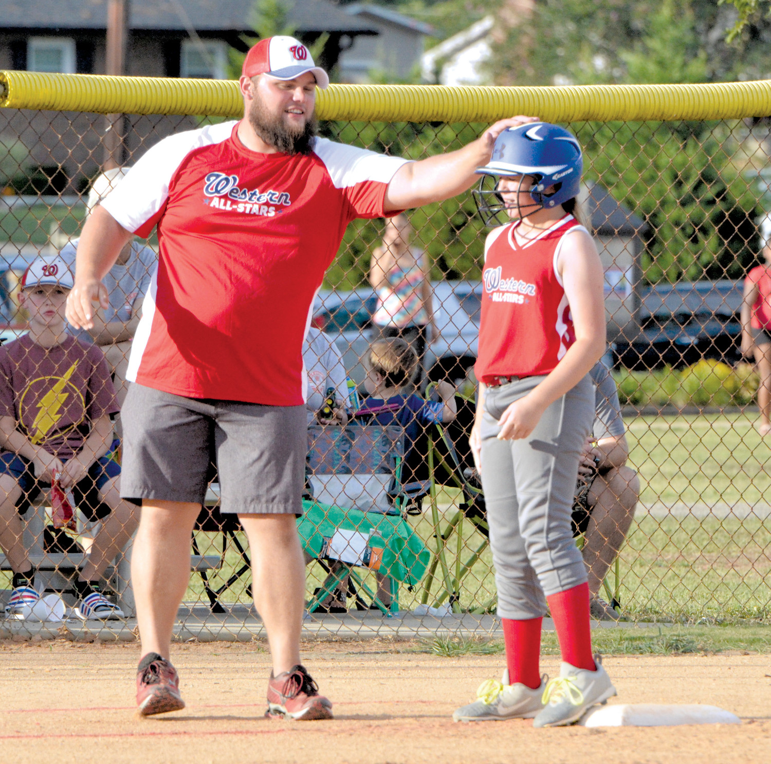 The Western Harnett 12U Tar Heel Softball All-Stars lost in the opening game of their District IV Tournament, 6-3, to Erwin on Monday evening. Here, the third base coach congratualtes a base runner for sucessfully stealing second and and third base in the first inning.