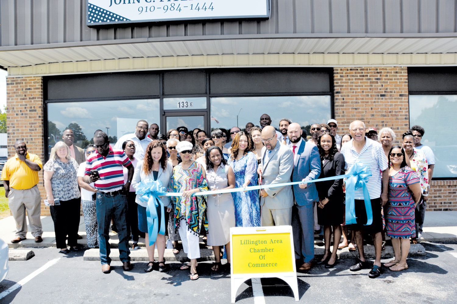 A large crowd came out last week for the ribbon cutting of the Fitzpatrick law firm in Lillington. Shown cutting the ribbon, in front, are Nichole Boone, Jake Fitzpatrick, Gerelene Goodman, Shatoria Parrish, Lolita Wynn, Pauline Fitzpatrick, John Fitpatrick Jr., Brennon Morton, Tenika Neely, John Fitzpatrick Sr., and Denise Williams.
