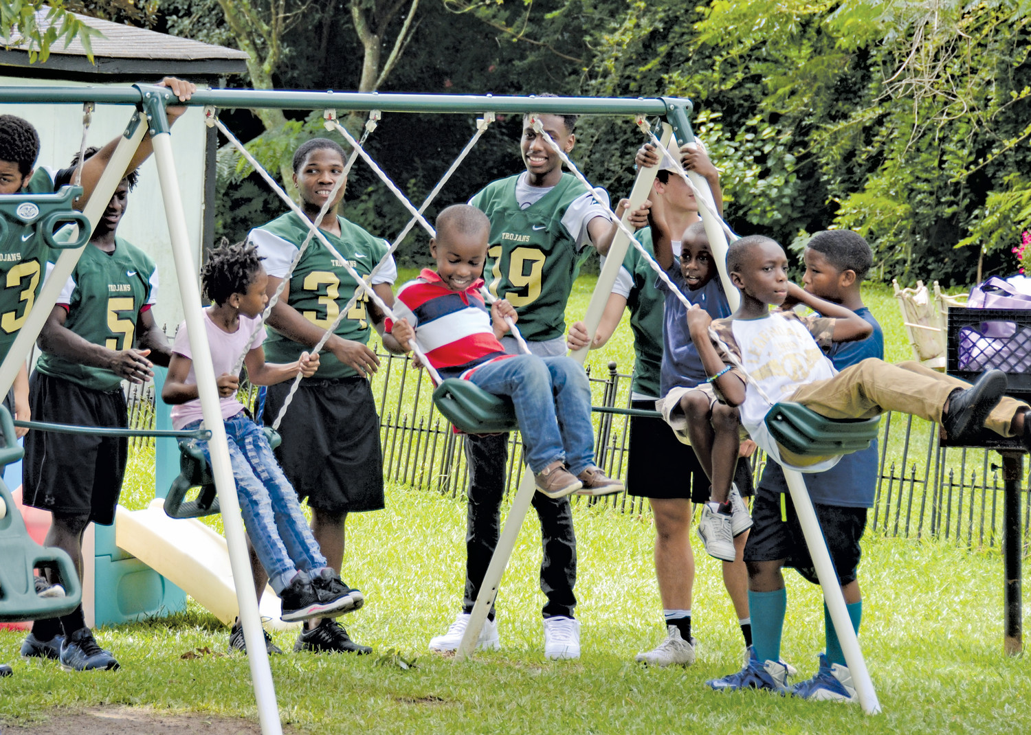 Part of the Four Leaf Clover Program in Benson involves getting the children in Benson out of the house. On Thursday, members of the South Johnston High School Trojans football squad joined the children. Here members of the team are helping some new friends get a little time on the swing set.