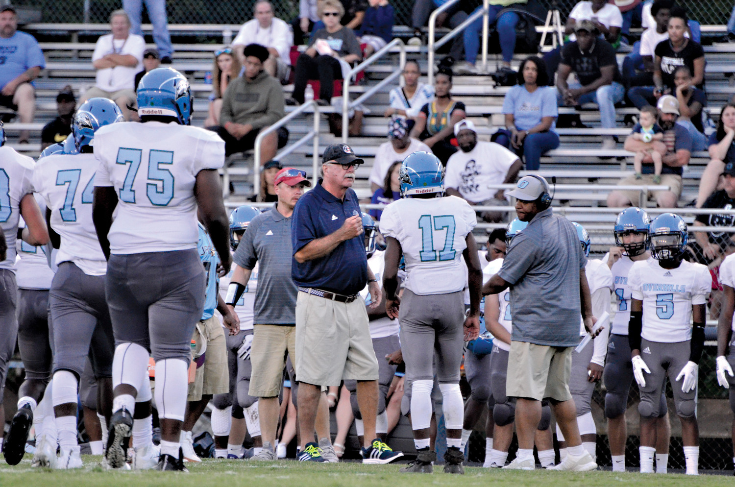 Last year, the Overhills Jaguars football program broke their coaching staff up between junior varsity and varsity. Head varsity football coach Mark Kirk didn't like how that worked out. So, Kirk, shown here at center, changed that, and made it so all varsity coaches help with the JV team, in order for the players to become more familiar with leadership.