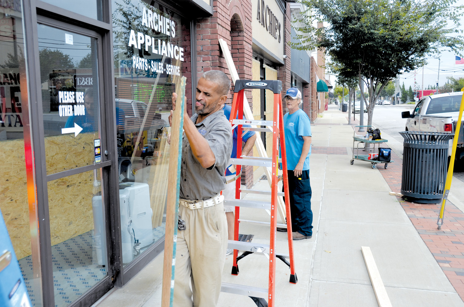 Area businesses took the time to ready for Hurricane Florence. Many windows and doors in the downtown area of Dunn could be seen covered with wood or plastic and anchored with tape and sandbags. One of those places was Archie's Appliances. Will Porter moves a piece of plywood while Don Wood and Gary Lee watch.