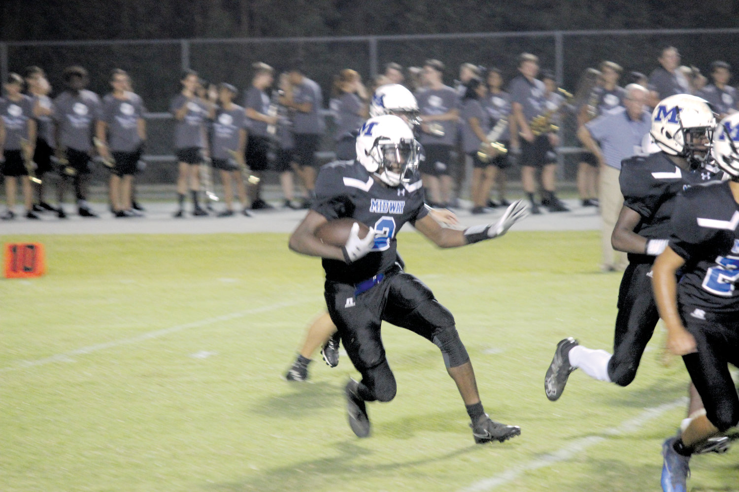 Dante Blue runs behind his blockers on Monday night. Blue had the lone score for Midway, a 92-yard reception on a screen pass.