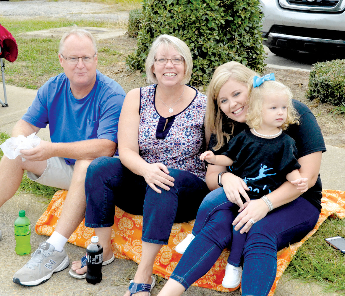 Enjoying Saturday's Denim Days Parade from their spot on the curb are Eddy and Tami Causey and Kensley and Kristen Young of Linden.