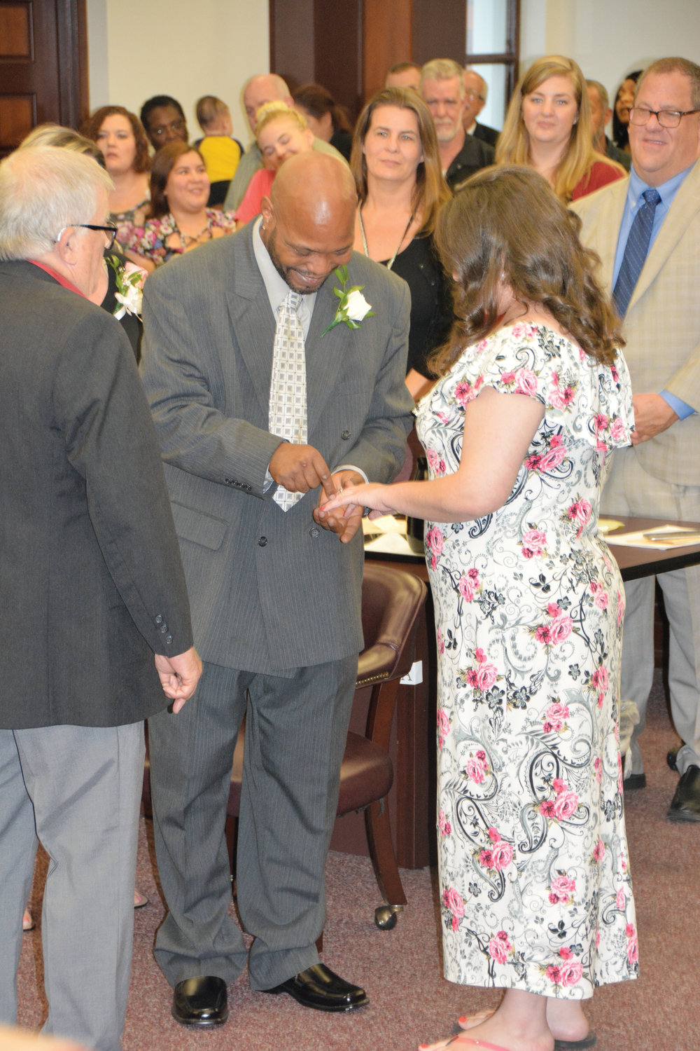 Veteran Hallitt Moore puts a wedding ring on the finger of his wife, Kristie, during the fifth anniversary celebration of the Harnett County Veterans Treatment Court which was held Wednesday. Magistrate Jerry Latta, left, presided at the ceremony.