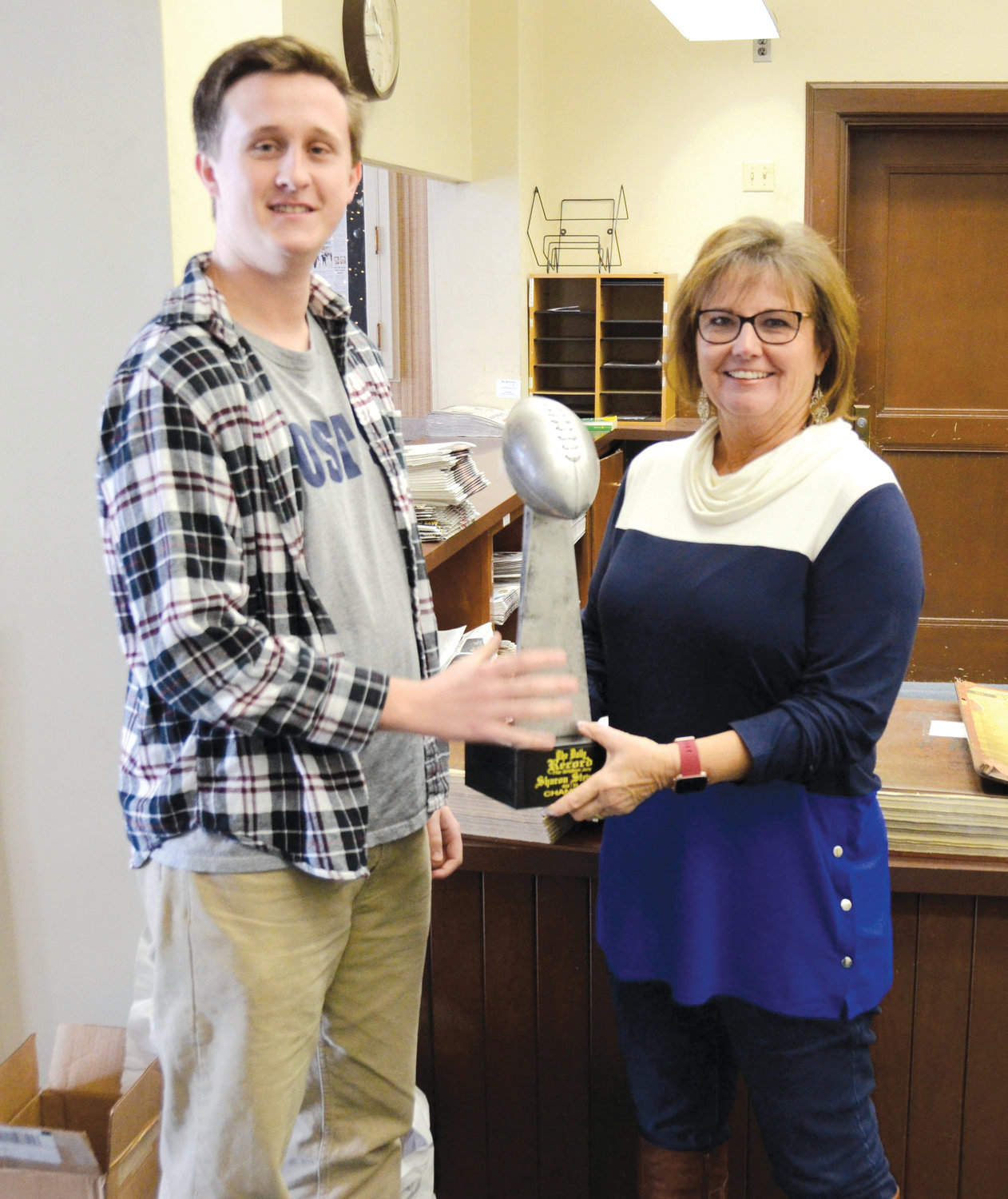 Sharon Stevens receives the Gridiron Jury trophy from Jacob Hancock, sports reporter at The Daily Record. The trophy was donated by Frazee's Trophies.