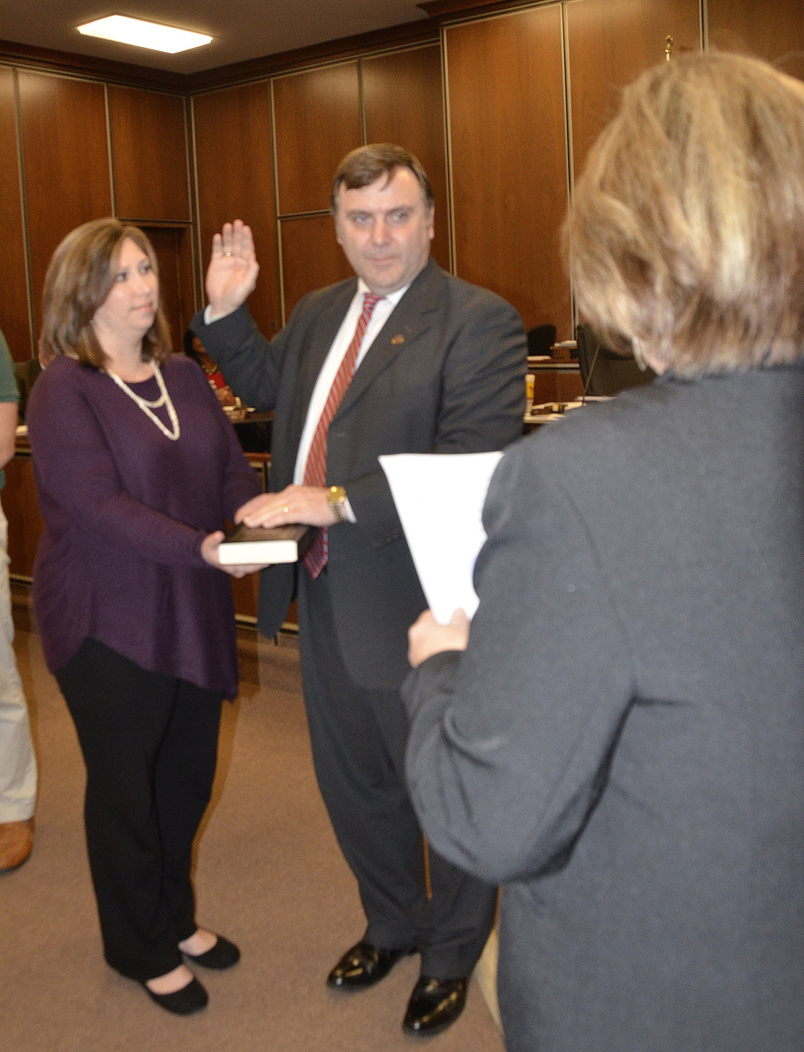 Dunn City Clerk Tammy Williams, right, administers the oath of office to new council member Dr. David Bradham as his wife, Meredith, holds the Bible.
