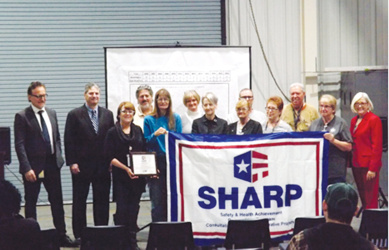 Saab Barracuda employees along with Labor Commissioner Cherie Berry display the SHARP flag during a recertification ceremony at its Lillington facility. This recertification is the third consecutive SHARP award for exceptional safety awareness and performance presented to Saab Barracuda.