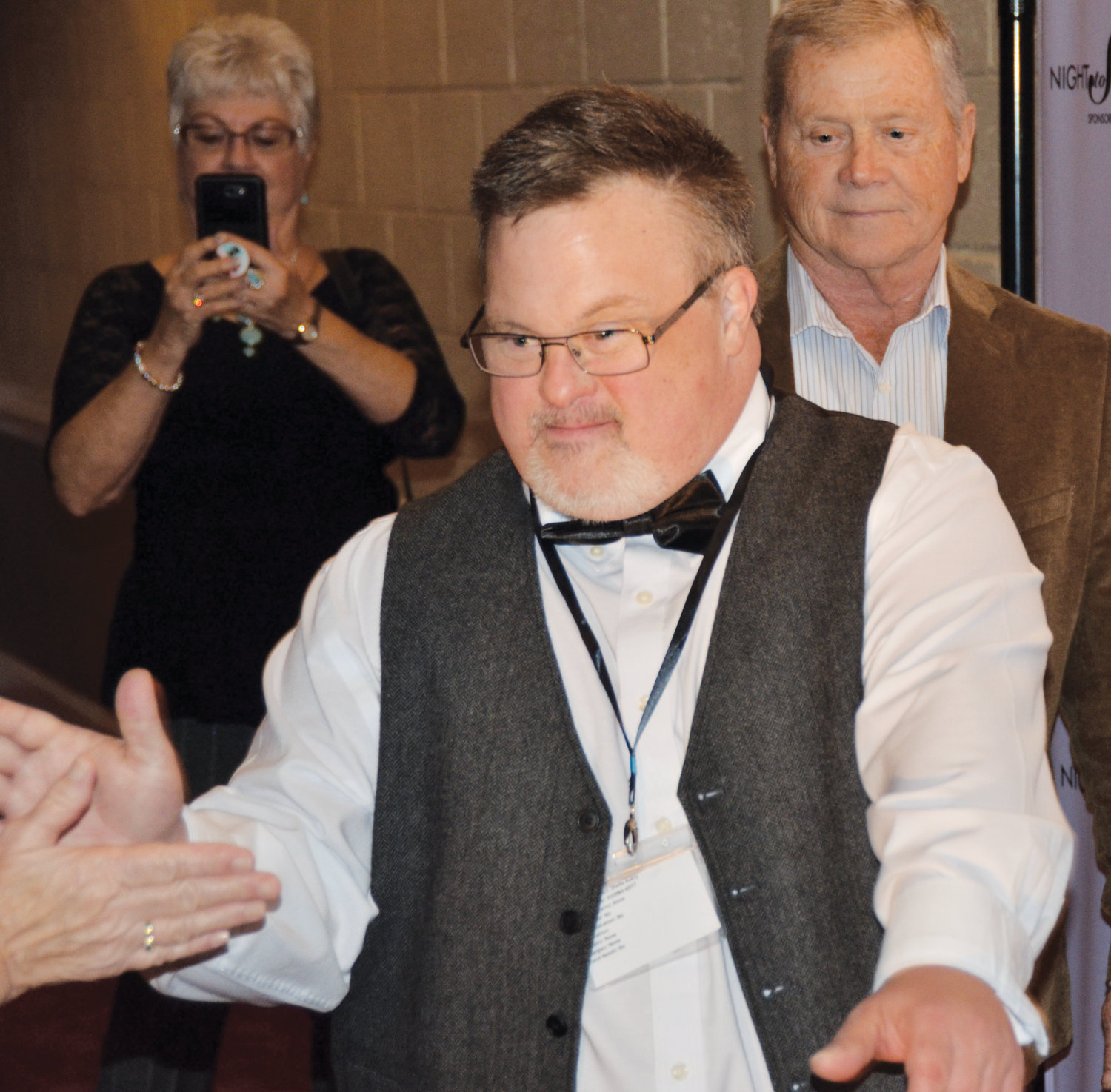 Larry Avery of Dunn high fives the paparazzi as he makes his way along the red carpet at Friday night's Night To Shine at the  Dunn Shrine Center. The event was sponsored by the Tim Tebow Foundation and hosted by the Mt. Carmel PFWB Church.