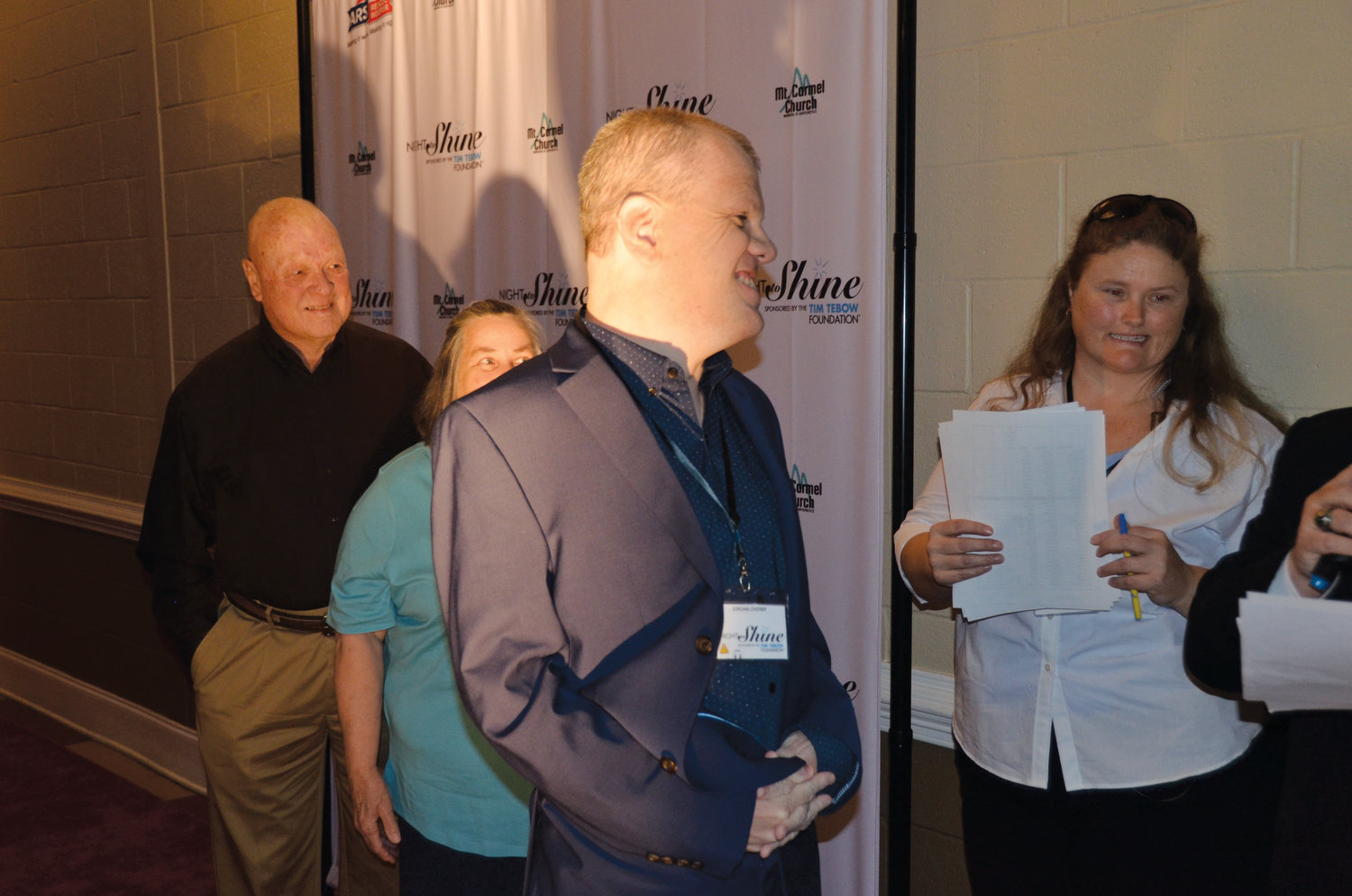 Scott Overby of Linden flashes a smile as his name is read and he's introduced to the crowd at the Night To Shine event at the Dunn Shrine Center Friday night. Scott was one of over 150 special needs guests to attend the prom. He's pictured with event organizer Jennifer Hardison and his parents, Larry and Debbie Overby.