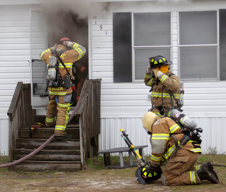 One fireman entering the home with a hose while two others prepare to follow behind.