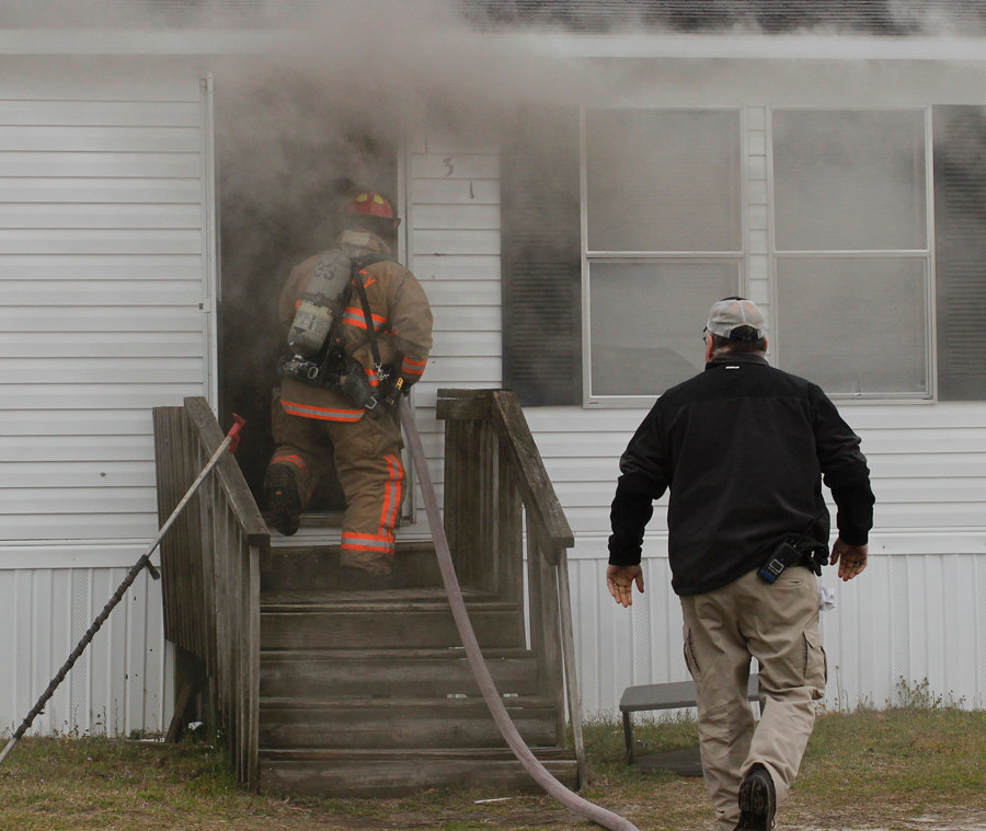 A fireman walking into the home with the hose looking to control and eventually subdue the fire.