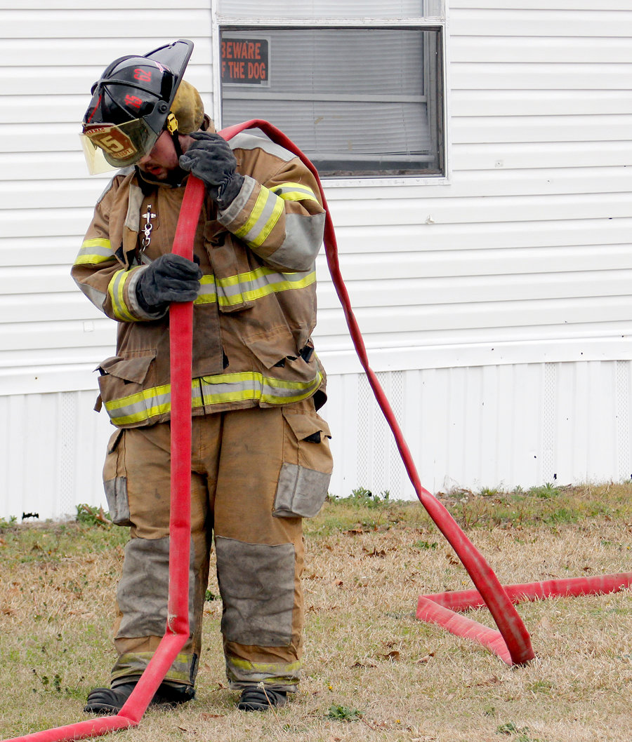 A fireman straightening the water hose in preparation to knock the fires down.
