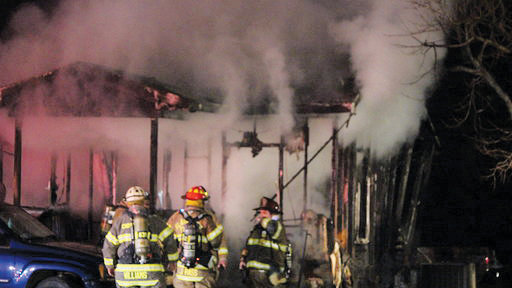 Firefighters battle a fire in the Plain View community Tuesday night. The fire started in the kitchen area of the home. Two people were left without a home as a result of the fire.