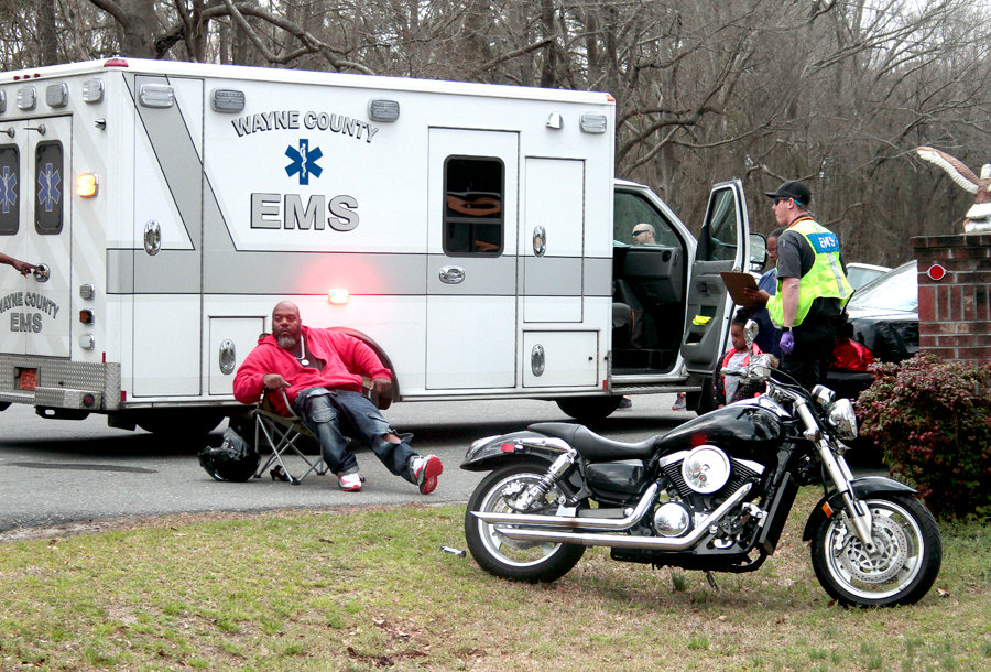 The driver of the motorcycle taking a seat after suffering minor injuries after the crash on Monday.