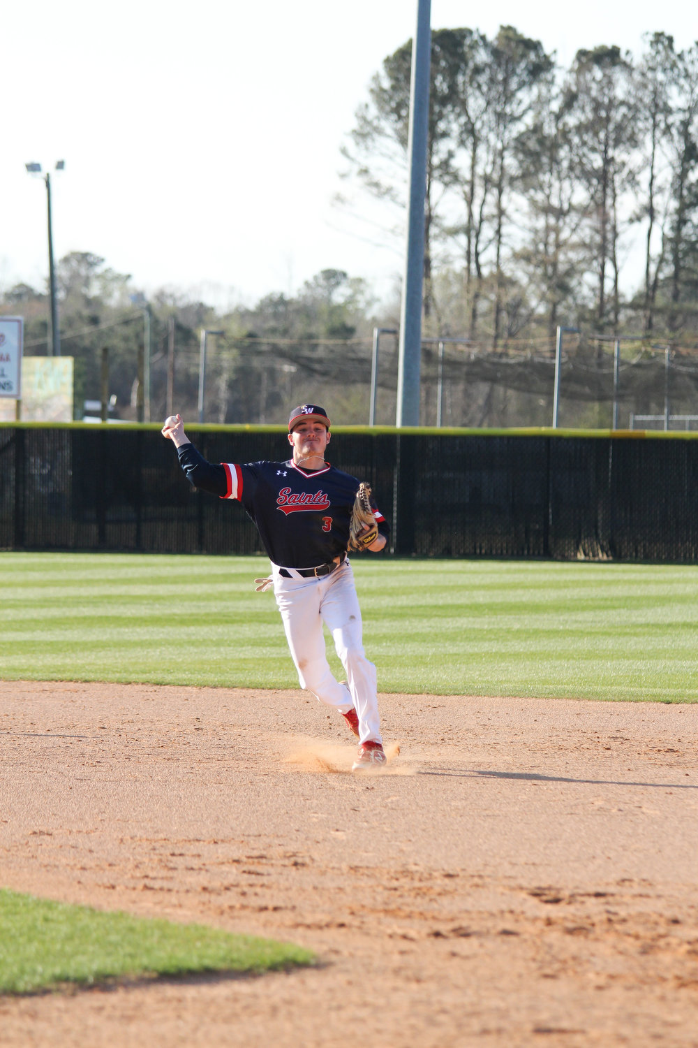 Senior Josh Raynor throwing to first for an easy out yesterday in the third inning.