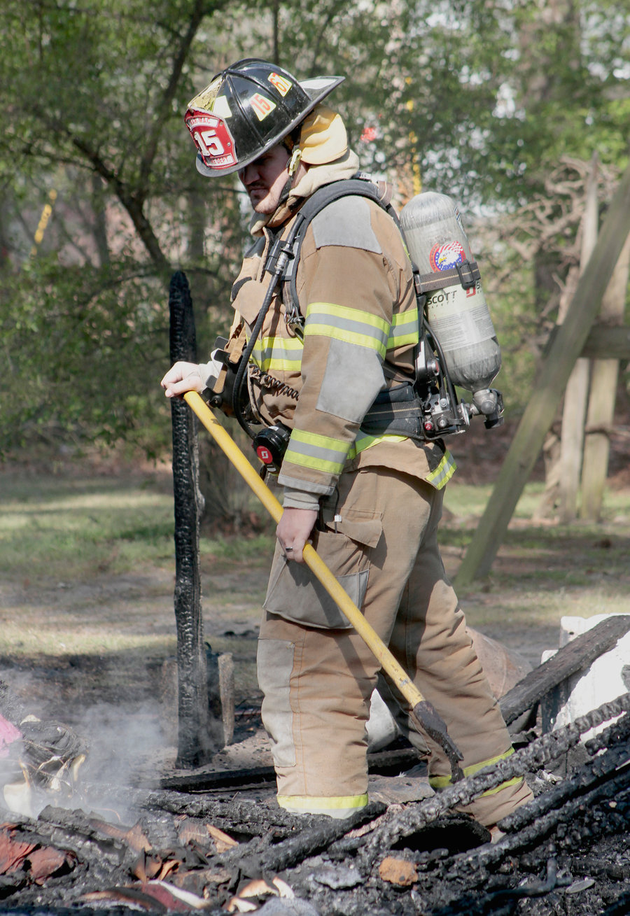 One of the firemen raking through the rubble making sure there are no more visible hot spots.