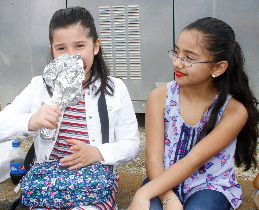 Carver Elementary students Shantella Martinez and Sophia Avila take a break to enjoy some food during the Pickle 