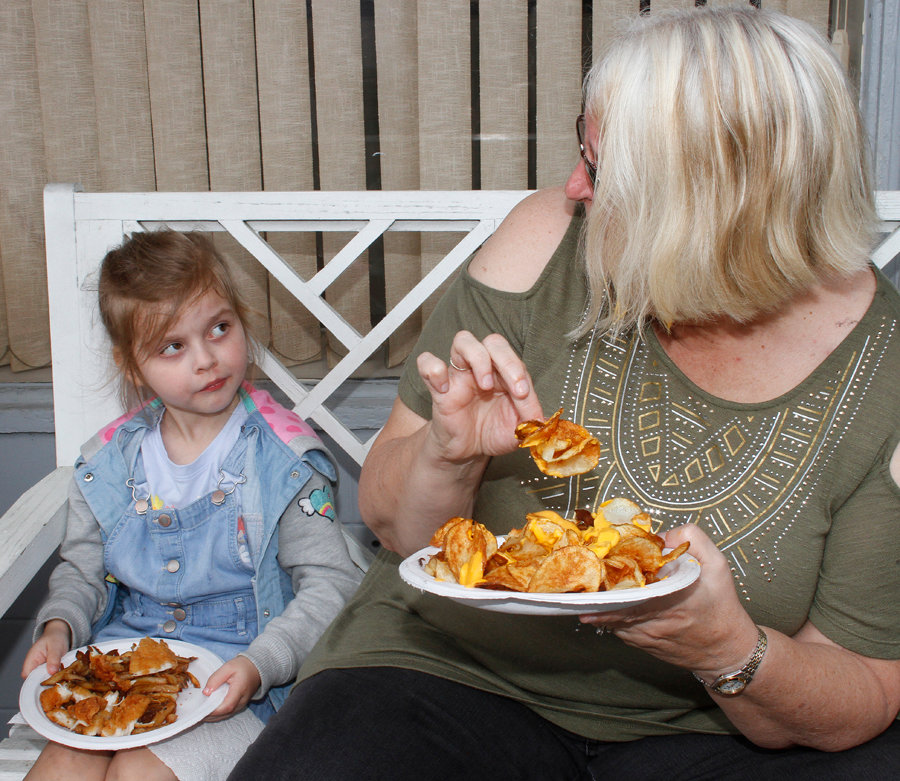 Five-year-old Sonja Melton and Robin Melton stop long enough to enjoying some fried chicken and curly fries Saturday at the North Carolina Pickle Festival.