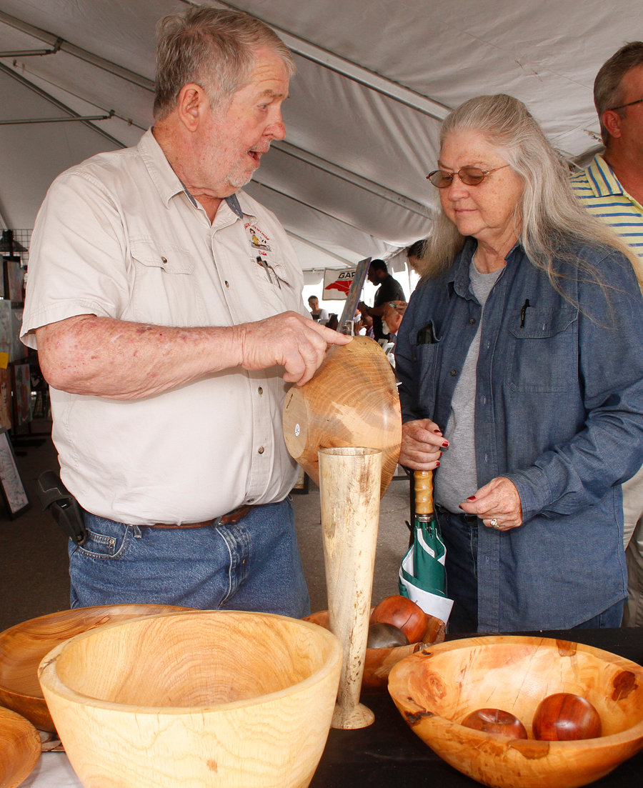 Dale Overman shows Lynn Barrett some of his wooden bowls at the Pickle Festival.