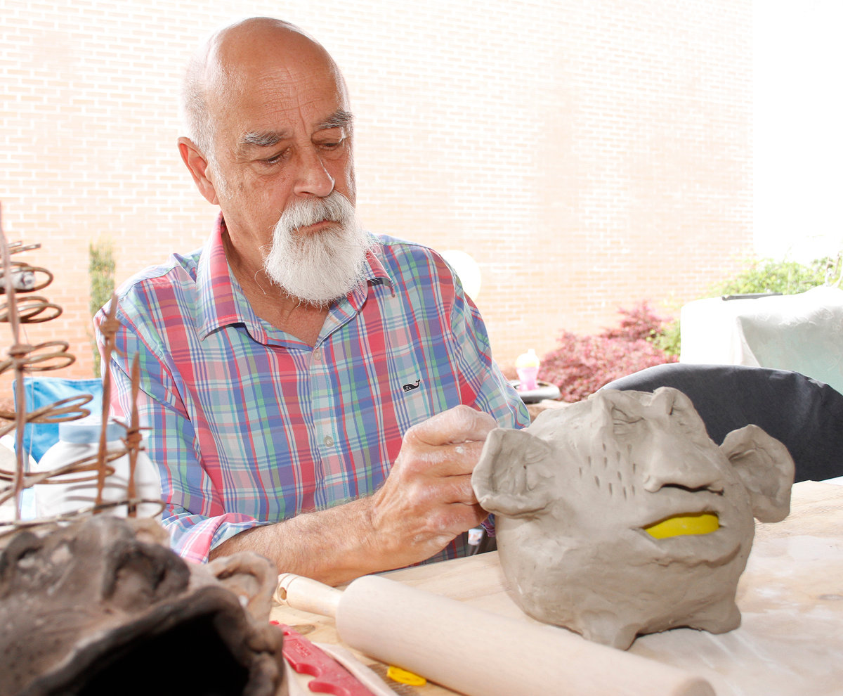 UMO Professor Larry Lean shows some of his clay art Saturday morning during the North Carolina Pickle Festival.