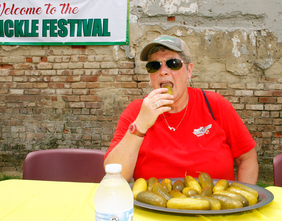 North Carolina Pickle Festival Chairman Julie Beck eats a dill pickle while getting ready for the Pickle Eating 