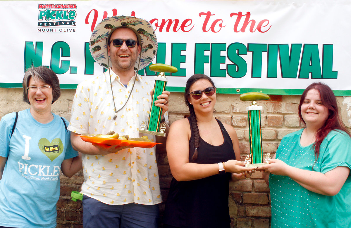 North Carolina Pickle Festival Co-Chairman Lynn Williams presented the trophies of this year pickle eating challenge winners Jacob Kreider and Kodi Smith and Patricia Davis. Smith and Davis tied for first place.