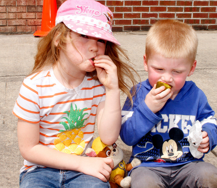 Madison Miller and her brother Andrew Miller take time to stop and eat their pickle during the Pickle Festival.