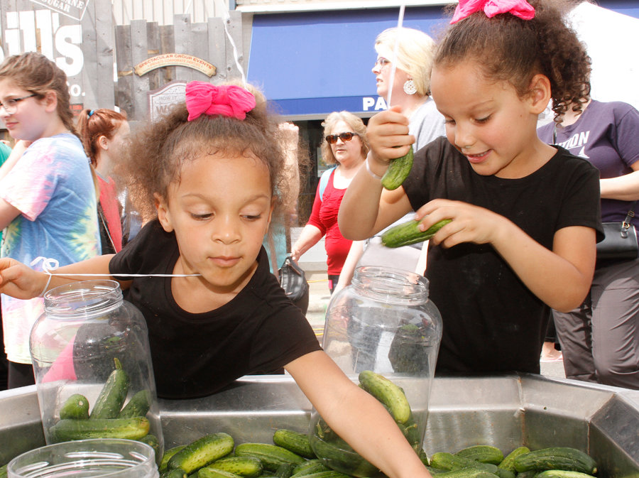 Johnya Bell and her twin sister Johnecia Bell see who could fill the pickle jars first during the Pickle Festival.