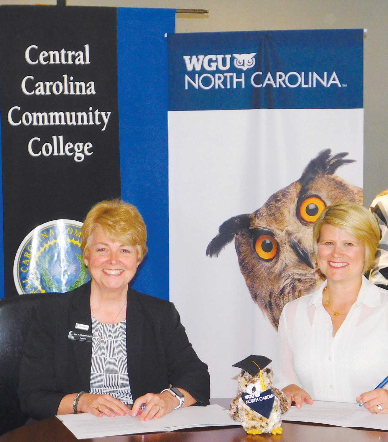 Central Carolina Community College President Dr. Lisa M. Chapman, left, and WGU North Carolina Chancellor Catherine Truitt  sign a Memorandum of Understanding that will ease the transition for CCCC graduates to pursue bachelor's degrees offered by WGU.