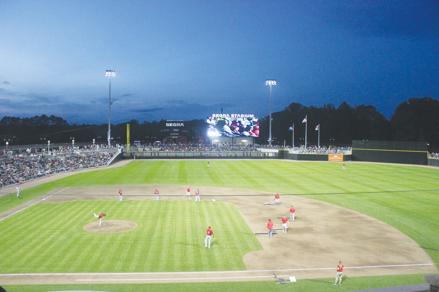 The Fayetteville Woodpeckers' grounds crew rakes the field in between innings Thursday night.