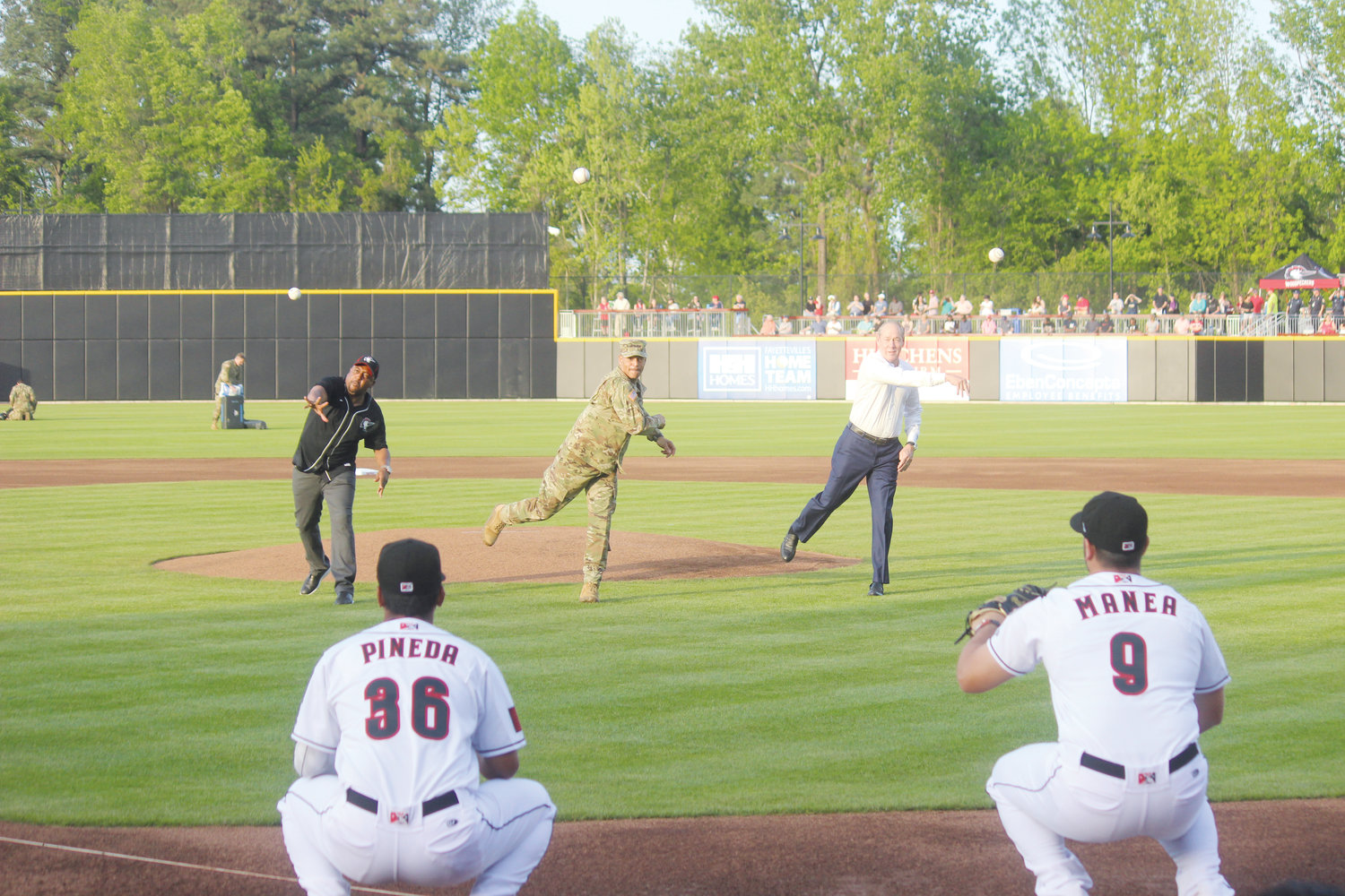 Fayetteville Mayor Mitch Colvin, Gen. Michael Garrett, commanding general of U.S. Army Forces Command and Houston Astros owner Jim Crane simultaneously throw out the opening pitch at the Fayetteville Woodpeckers' home opener Thursday.