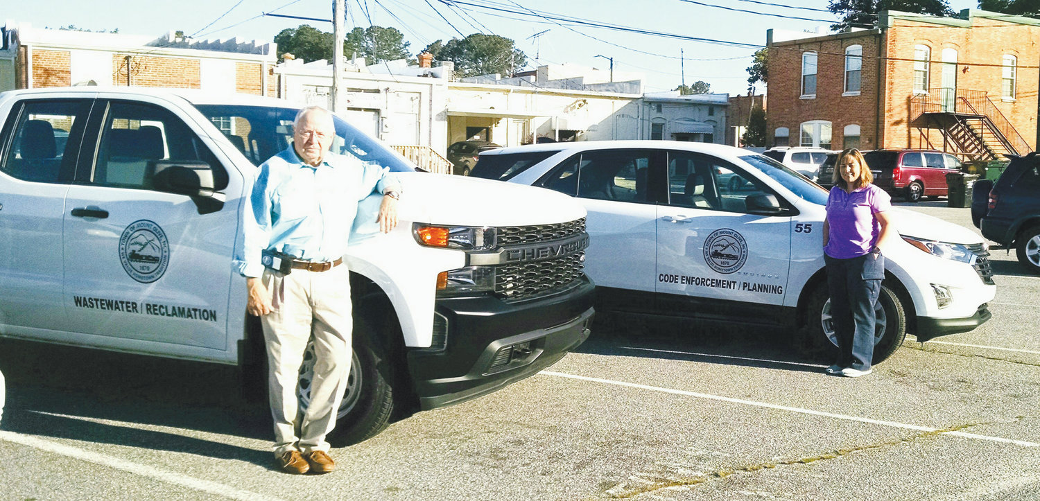 Two new vehicles have been added to the town's fleet. In the forefront, town manager Charles Brown stands by a new Chevy Silverado work truck for the wastewater treatment plant, and code enforcement officer Erin Lambert stands by her new Chevy Equinox. These are the first of 19 new vehicles under a new vehicle replacement program.
