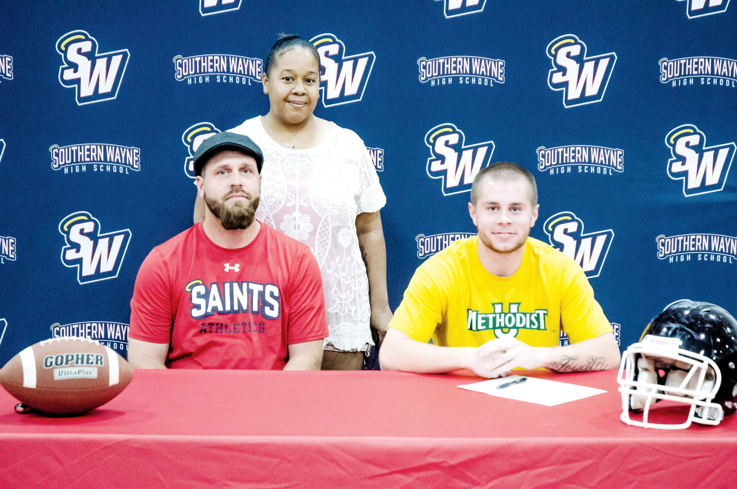 Dylan Denning gets ready to sign his letter of intent to play for Methodist University, with his dad, Dwayne, and stepmom, Laqueila Denning.