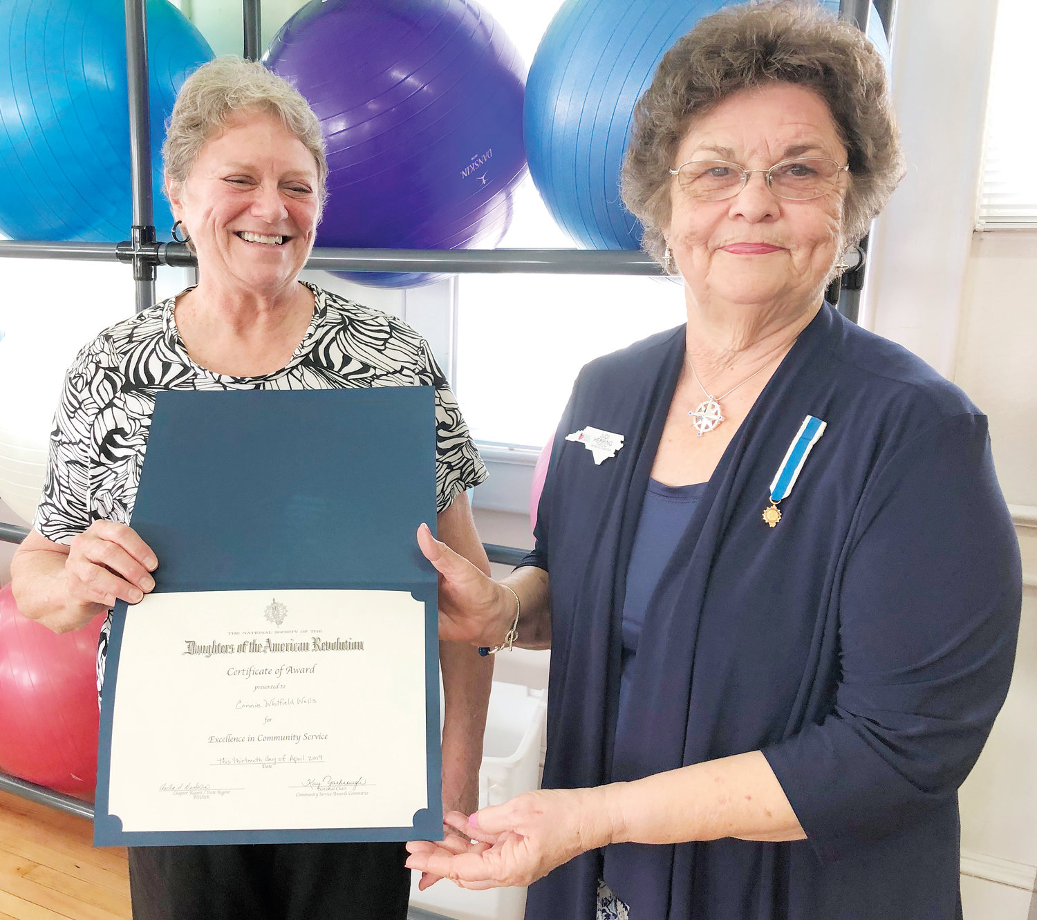 Connie Wells, right, is presented a certificate and pinned upon receiving the community service award by Judi Herring, registrar of the local Carolina Patriots Daughters of the American Revolution chapter of Mount Olive.