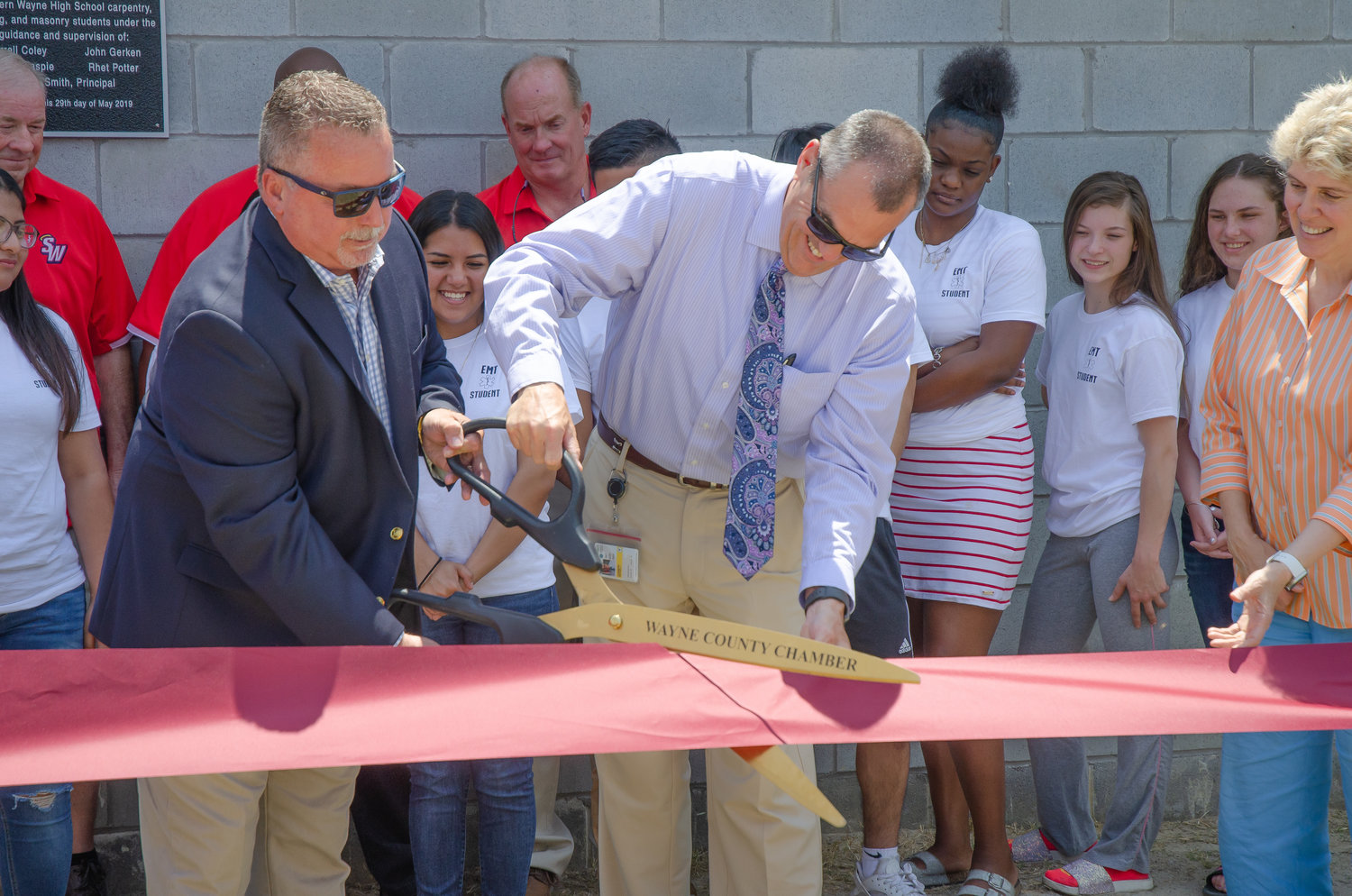 Wayne County Public Schools Board of Education Chair Chris West, along with Superintendent Dr. Michael Dunsmore, cuts the ribbon for the opening of the new EMT Training facility on Southern Wayne High's campus.