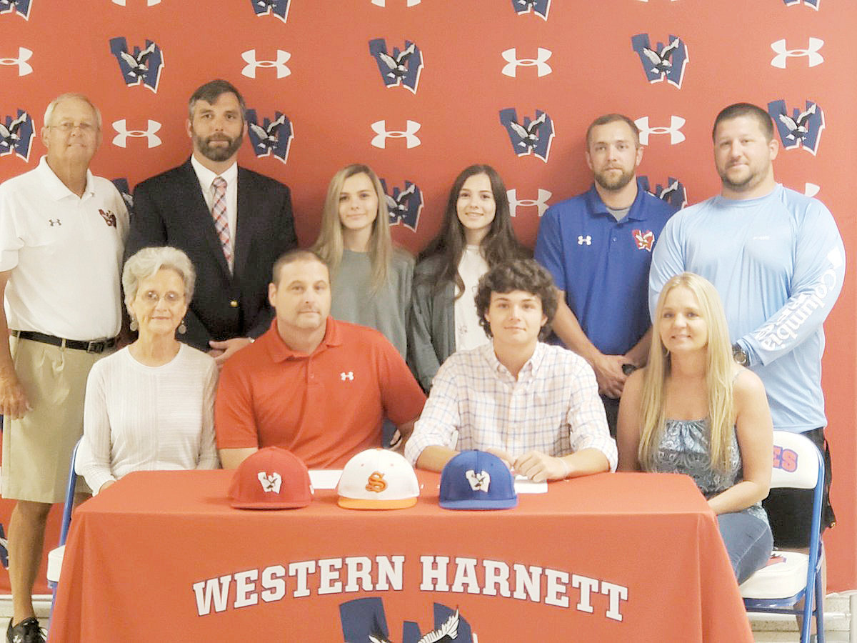 Chase Holder, center, is seated with his grandmother, Linda Holder, his father, Keith Holder, and his mother, Terri Holder. Standing are Athletic Director Russell Taylor, Principal Matthew Price, Chase's sisters, Kendall and Kaylee Holder, head coach Dalton Hardee and assistant coach Blake Culbertson.