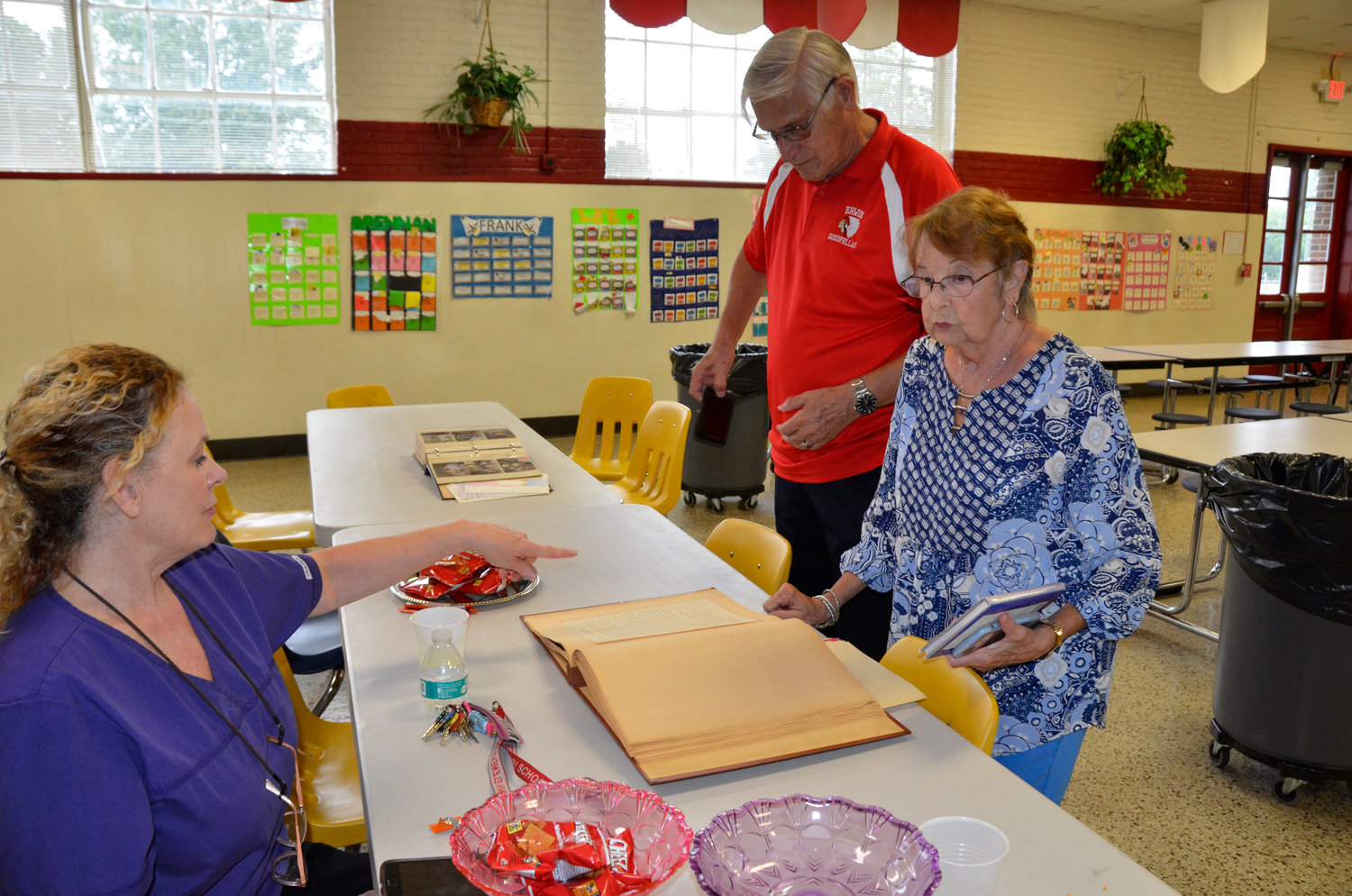 Erwin Elementary cafeteria manager Johnna Fann shows Jim and Jean Bradley of Erwin scrapbooks made by former students that she has found over the years at the school. She plans to give the books to the Erwin Historical Society.