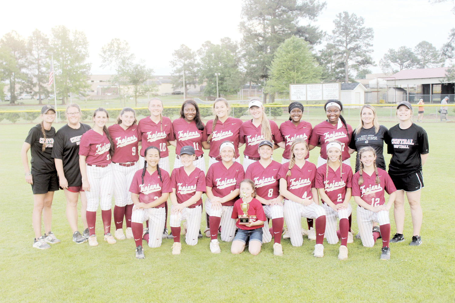 Harnett Central's softball team gathers after winning the Tri-County Conference Tournament Championship. Kneeling, from left, are Ella Prince, Mikaela Goss, Shelbie Gill, Emily White, Lauryn Waddell, Kylee Frailey and Laurie Blackwell. On the back row, from left, are assistants Ashlee Crewe and Olivia Scarborough, Fallon Wimberly, Jessie Dillon, Lyndsey Brewer, Marcayla Jones, Kolby Medlin, Ansley Lee, Ivanna Jones, Amaya Bell, coach Chelsey Cabe and assistant Morgan Hall. In front, with the trophy, is bat girl Leah Brewer.