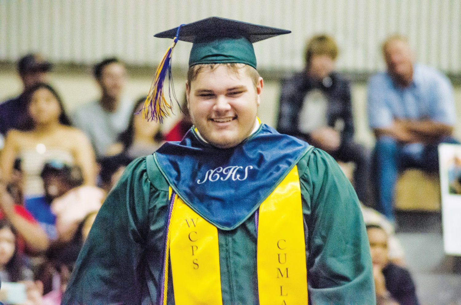 Aubrey Pollock smiles as he receives his diploma at Spring Creek's graduation ceremony.