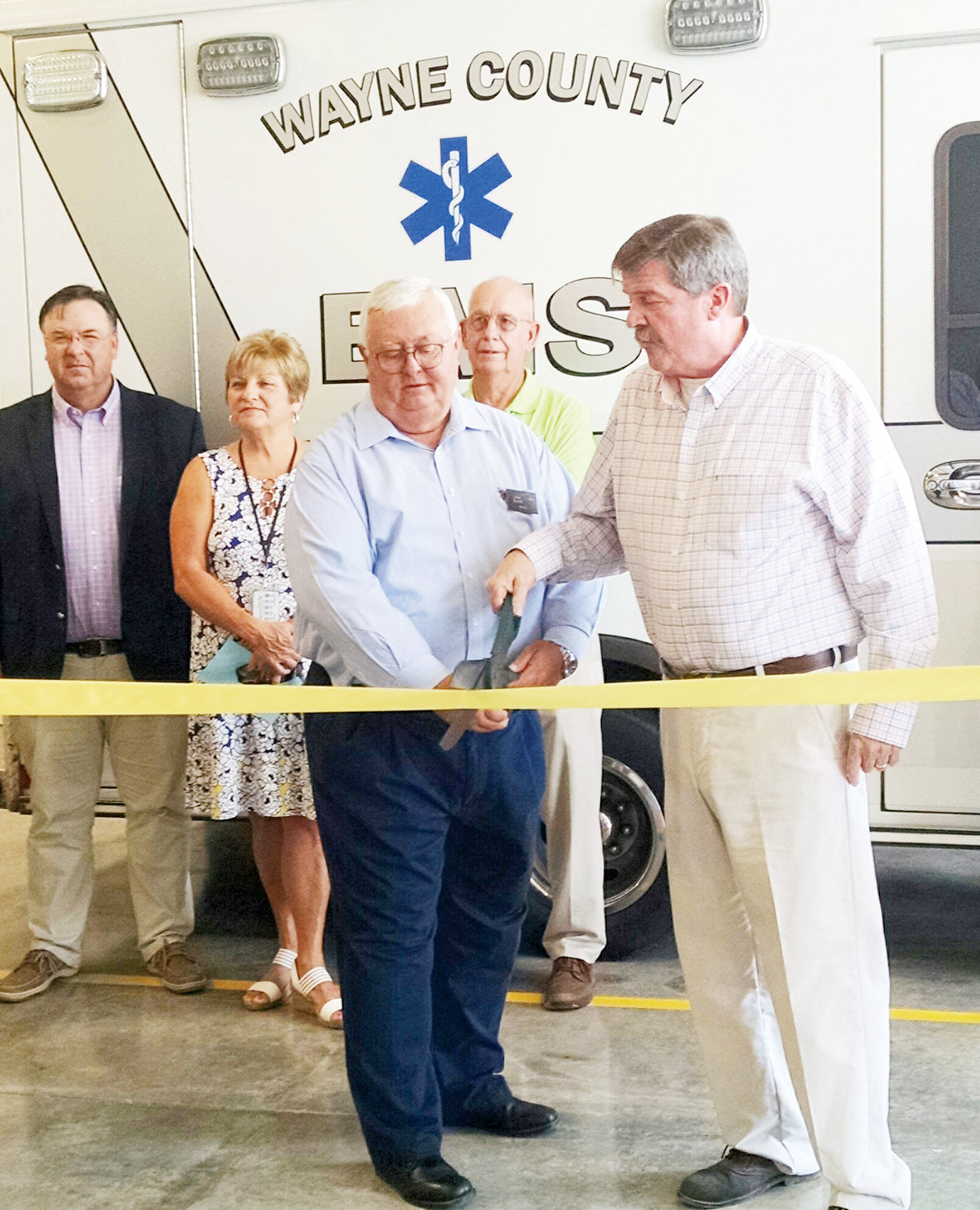 Mount Olive Mayor Joe Scott, left and Joe Gurley, chairman of the Wayne County Board of Commissioners, cut the ribbon to open the new $500,000 EMS No. 9 rescue station in Mount Olive. In the background, from left is County Manager Craig Honeycutt, EMS Director of Administration Nannette Sutton, and Wayne County Commissioner Wayne Aycock. This station is the third of four new EMS facilities in the county aimed at reducing rescue response time to 8 minutes.