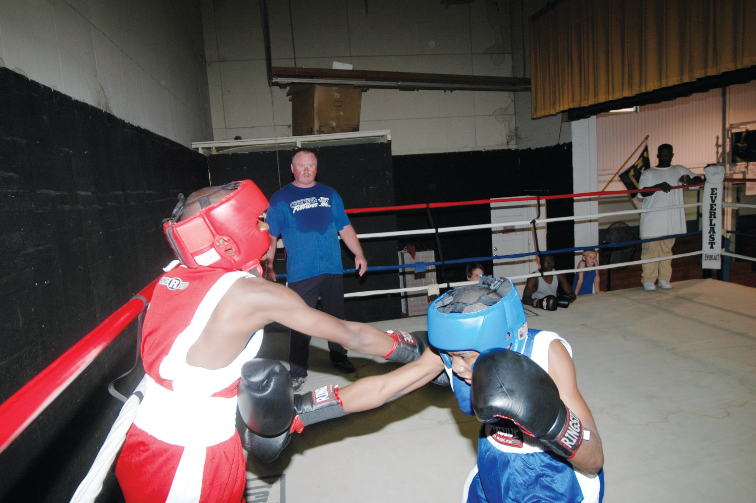 Harnett County Sheriff's Office PAL program director Mark Hornsby supervises as two boys spar in the boxing ring. Hornsby helped organize the Christy Martin Title Boxing Invitational that will take place at Harnett Central High School this week.