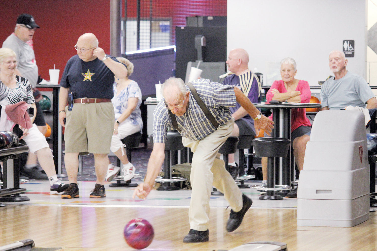 Lawrence Rogers gets down low to bowl a strike at Buffaloe Lanes in Erwin on Monday.