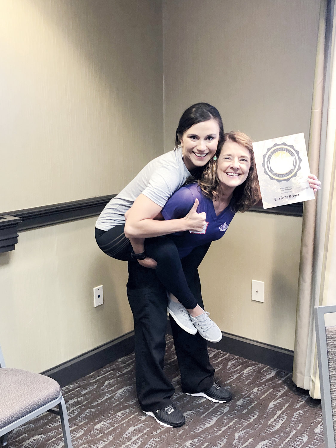 Heather Lane rides on the back of Bliss Day Spa owner Tammy Honeycutt to get their Best of Harnett award. The spa was nominated and voted as the best place to get a massage in the area by The Daily Record readers.