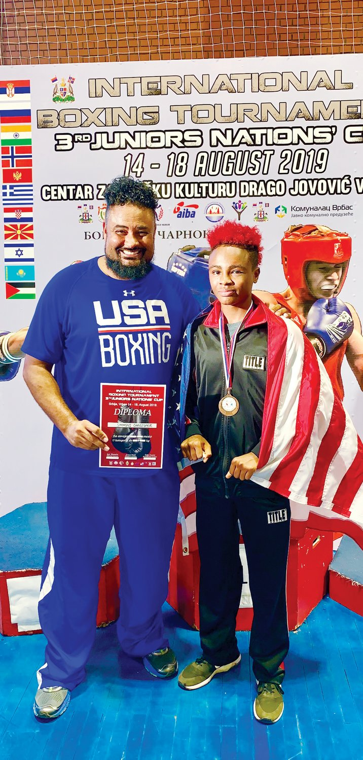 Chris Simmons, left, and his son, Christopher, stand together at the Junior Nations Cup in Serbia. Christopher finished third in the competition and took home the bronze medal.