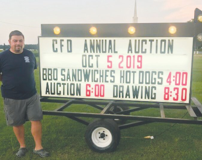 Calypso Fire Chief Brandon Cashwell is seen here checking out the promotional sign for the department's upcoming auction fundraiser.