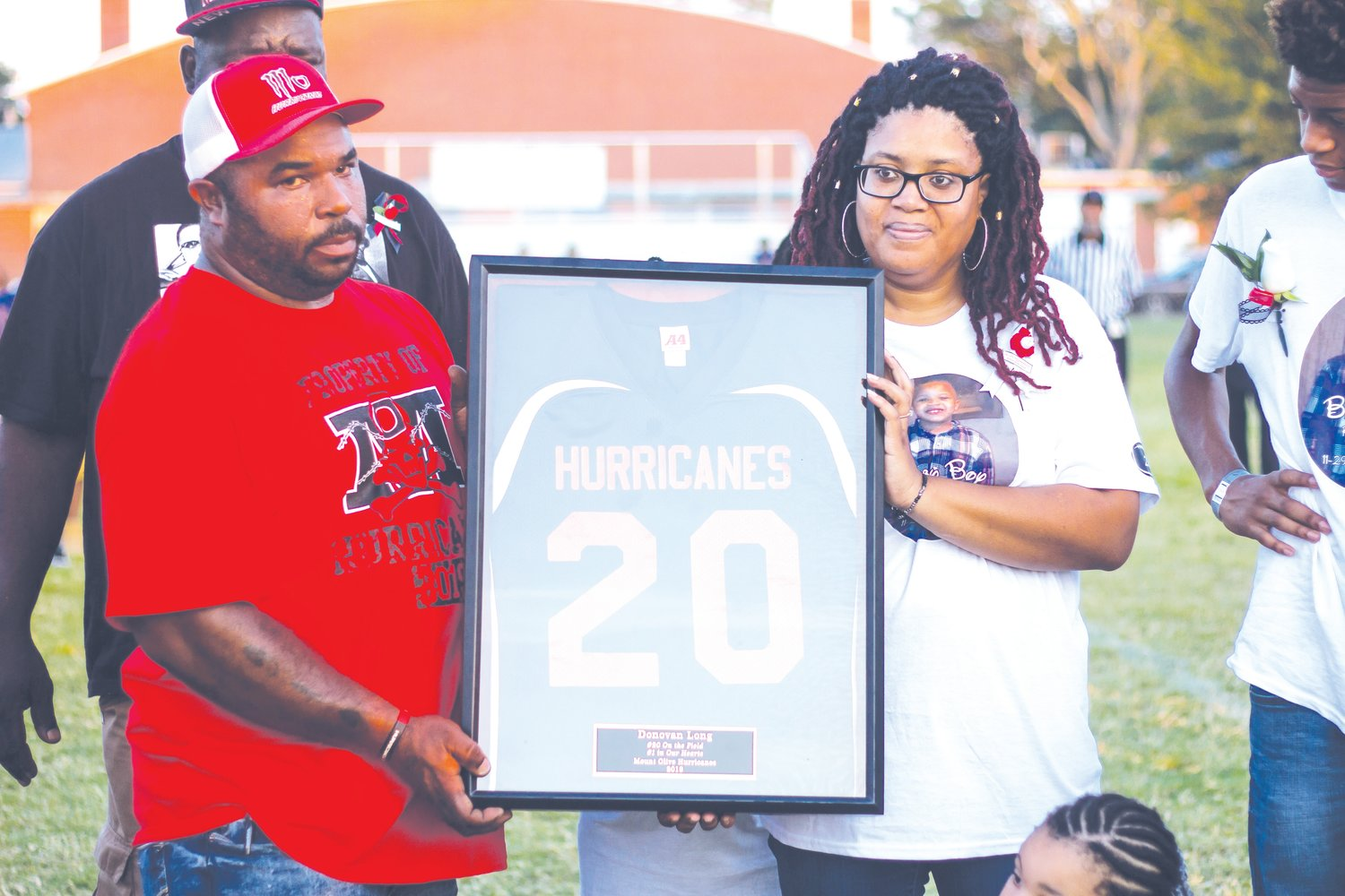 Coach Darion Kelly and Donovan Long's mother Lacretia Goodman stand together with Long's jersey. The Hurricanes have retired Donovan's jersey so that no other player will ever wear No. 20 for the Hurricanes in honor of Donovan.