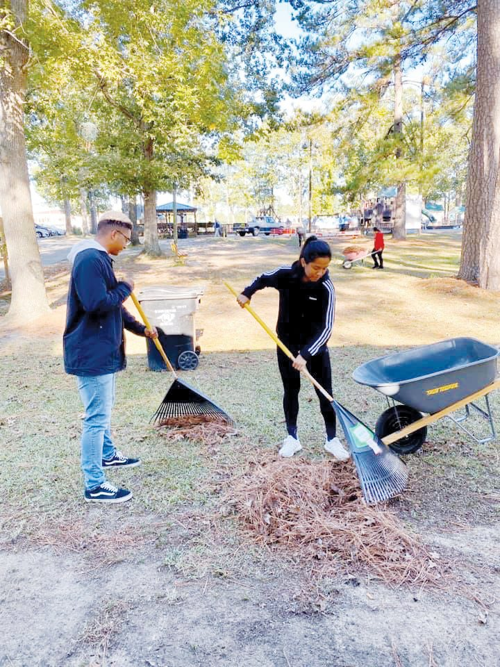 Soccer players Anthony Wrenn and Christina Galvan rake up leaves during the cleanup at Westbrook Park.