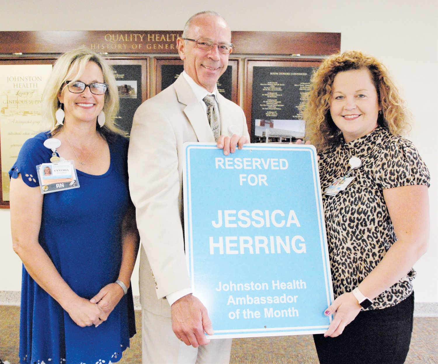CEO Chuck Elliott congratulates Jessica Herring, a peer review nurse in the quality department, on being named Ambassador of the Month. At left is Cynthia Holloman, director of quality management and regulatory compliance. In addition to a parking sign and designated parking spot, Herring will receive eight hours of paid time off.